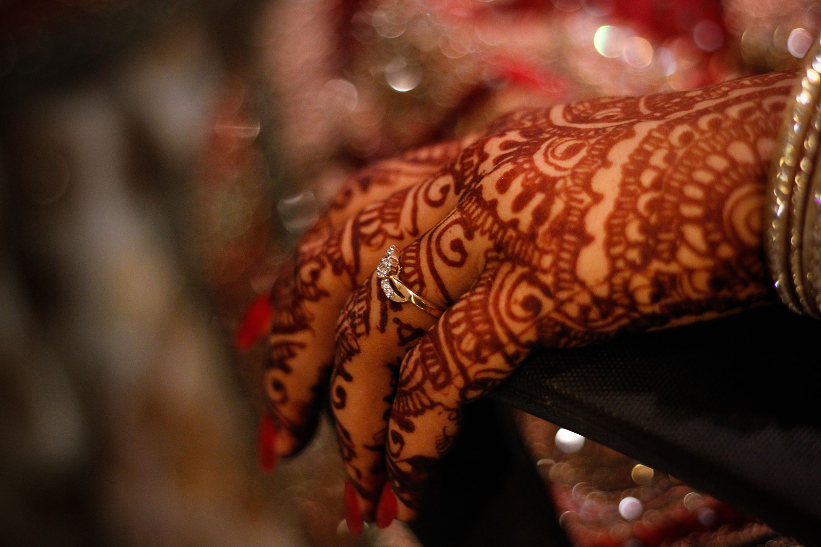 Bride's hands with beautiful mendhi with wedding Ring