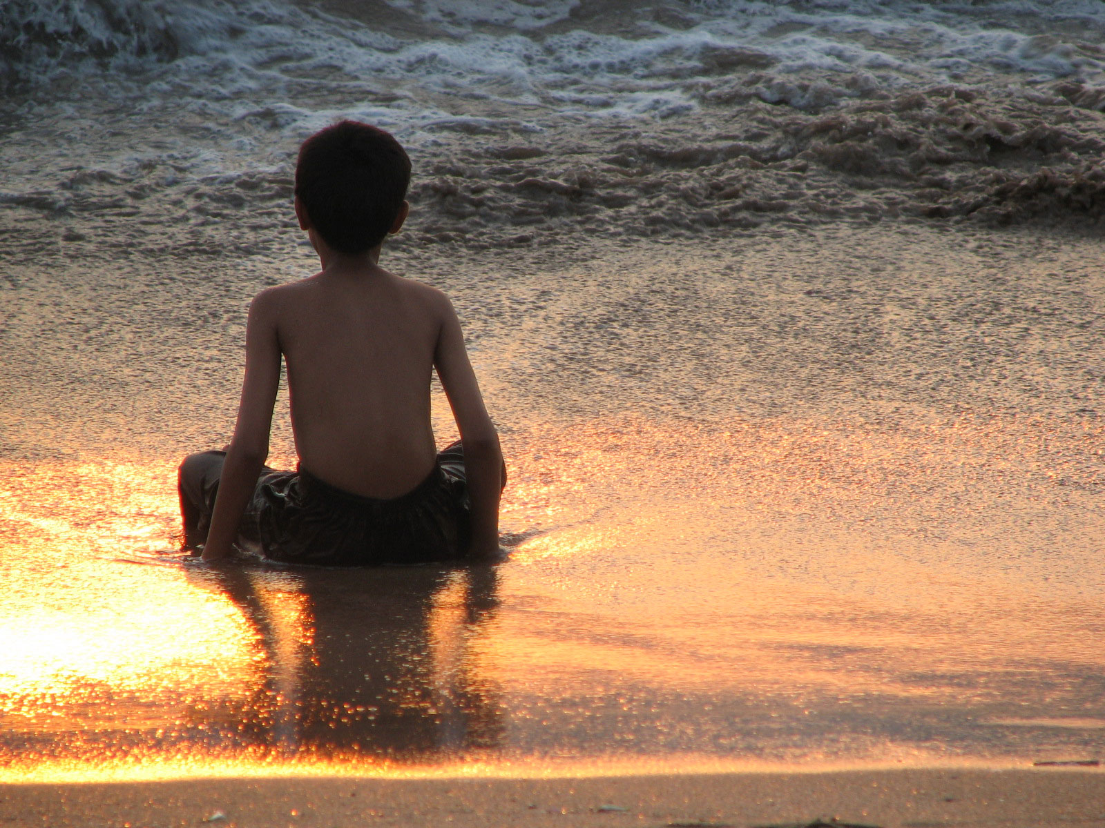 Boy sitting at the beach beautiful lighting sunset