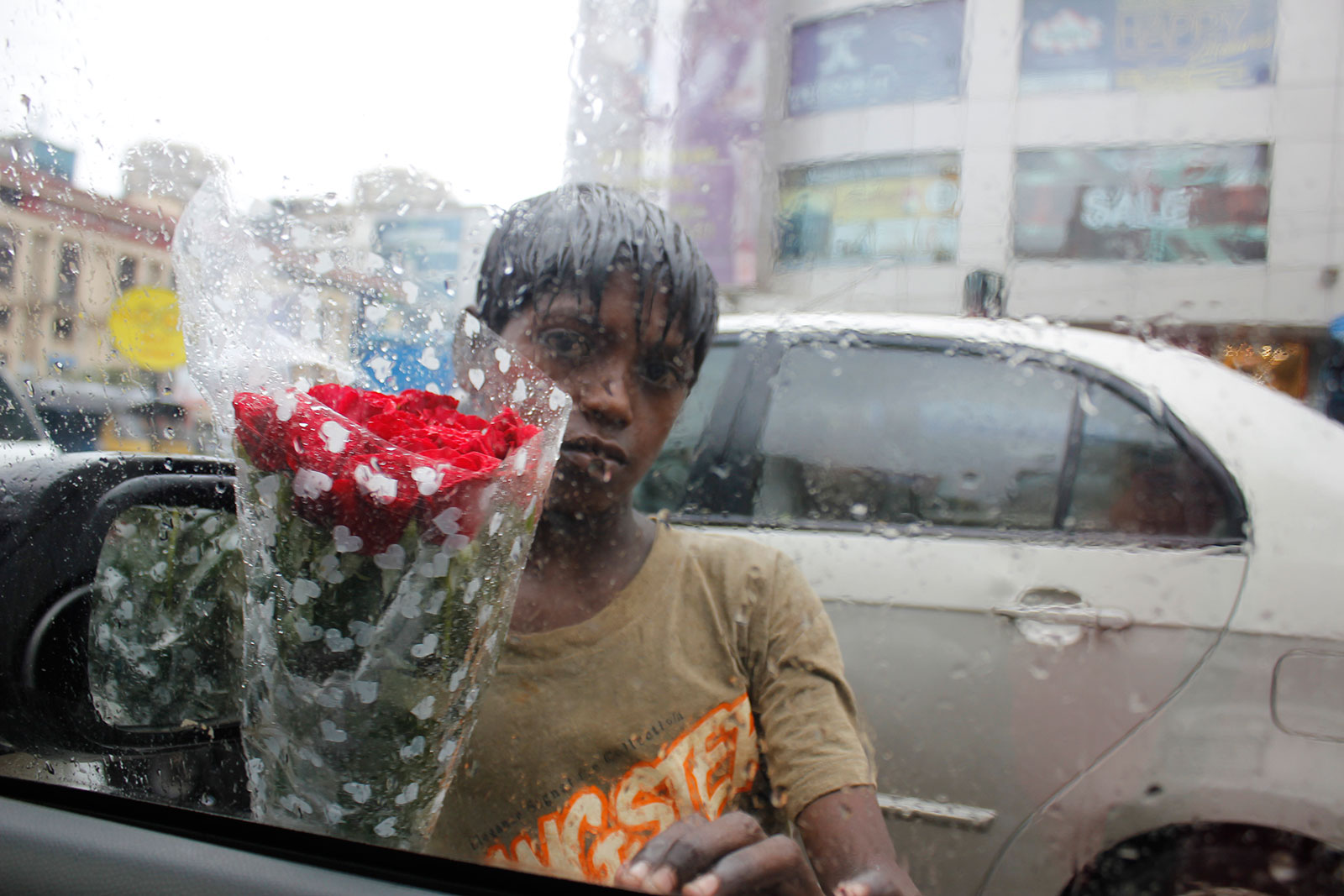 potrait shot from car of a boy selling frowers in the rain