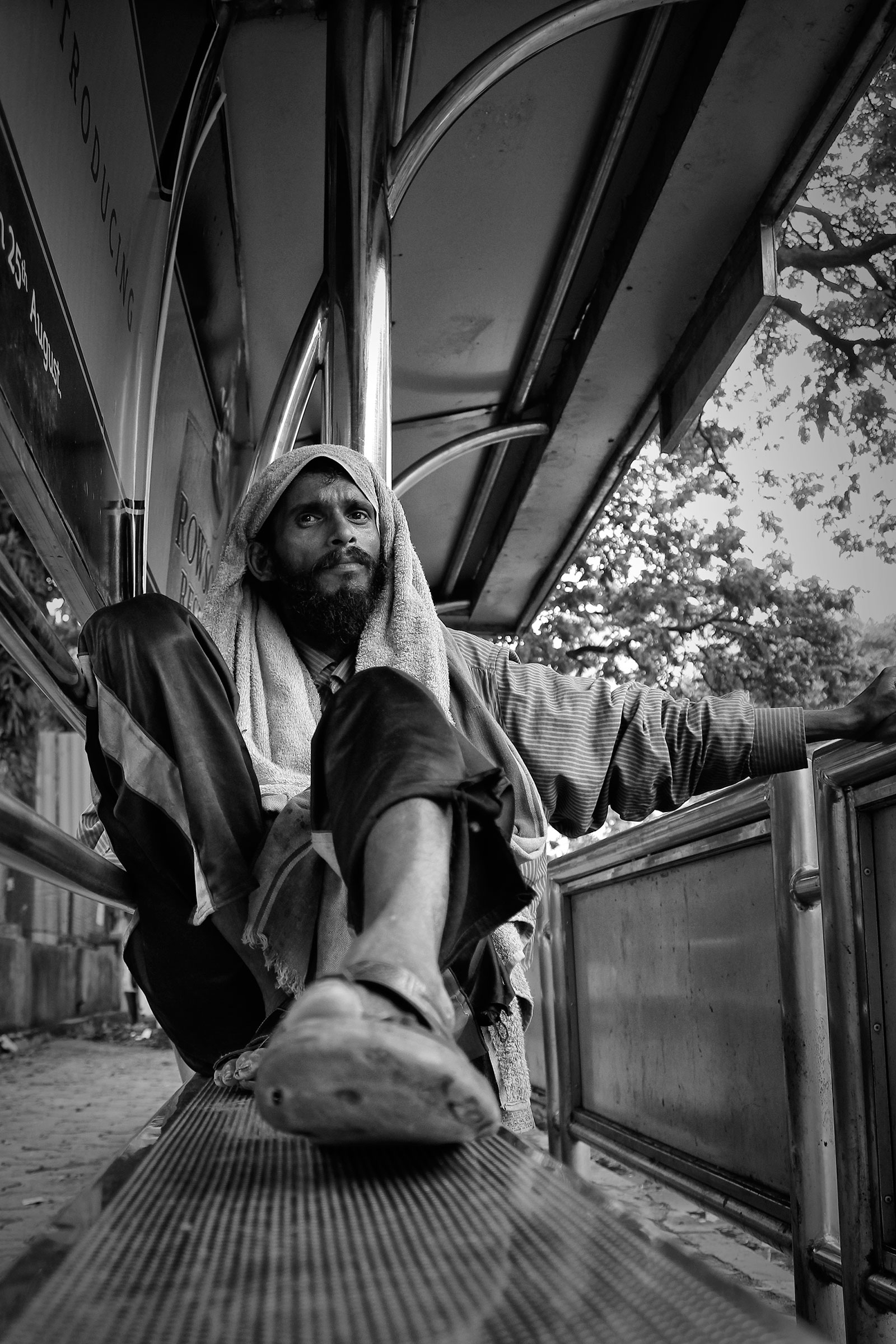 Black and white portrait of a homeless man at a bus stop