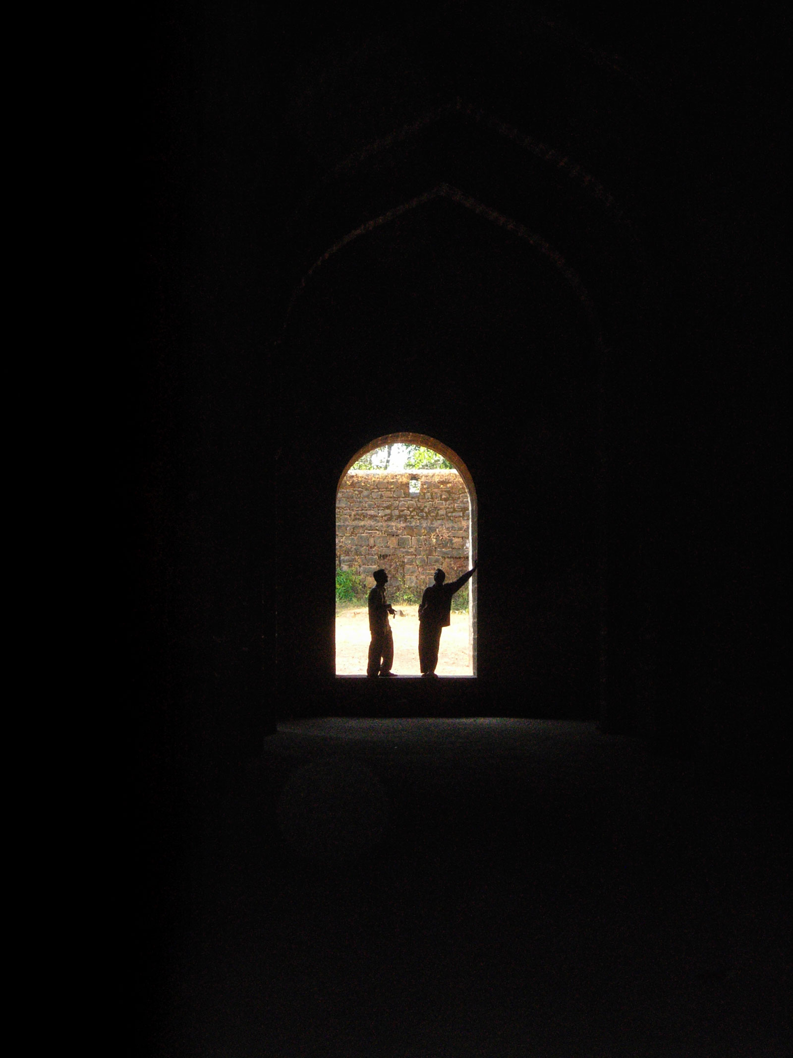 Two men standing at under an arch of monument in india