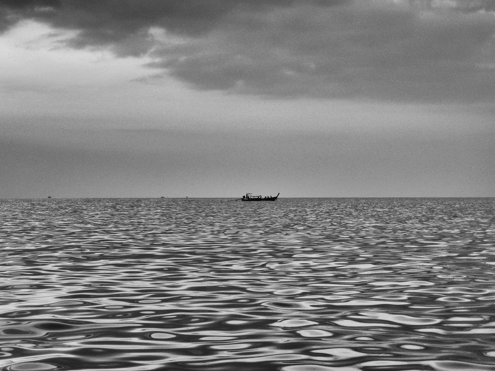 Black and White Photo of Sea with a fishing boat in the centre